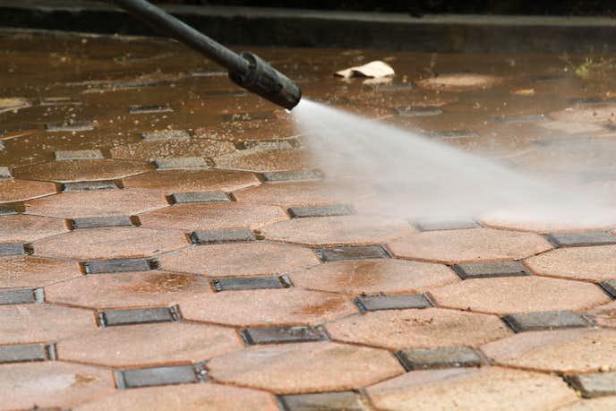 高圧洗浄機で庭のコンクリートを掃除している
