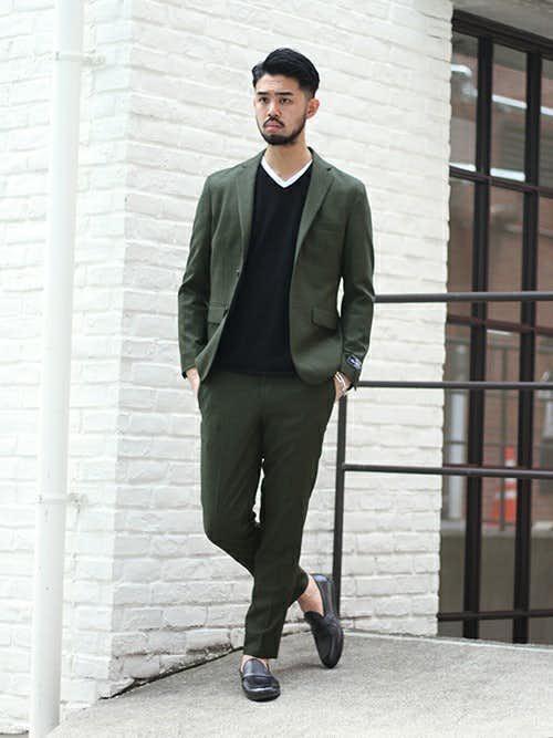 カーキジャケットと黒ニットの重ね着スタイルのメンズコーディネート