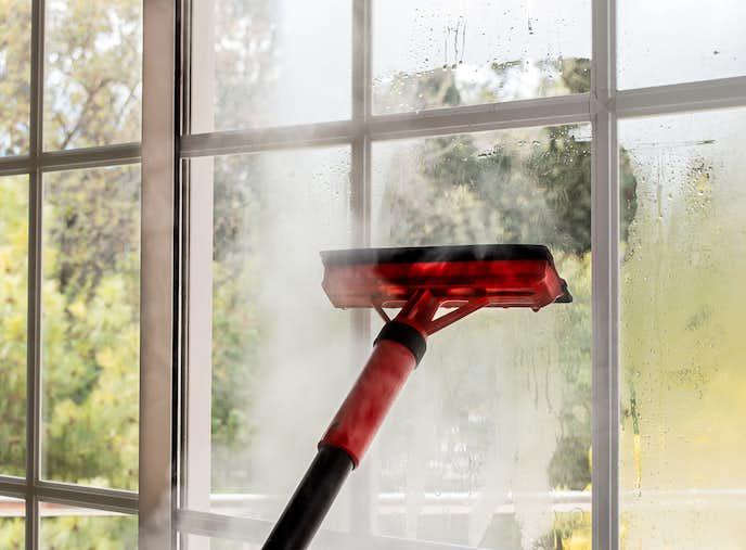 高温スチームクリーナーで窓を掃除する人
