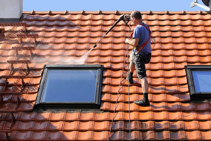 高圧洗浄機で家の外壁を掃除している男性