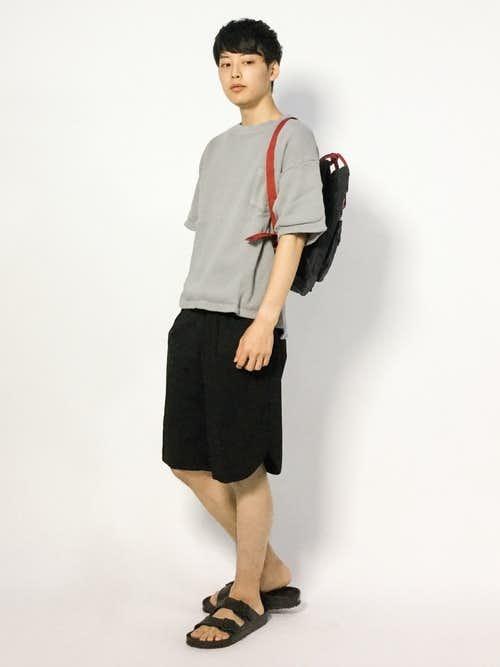 ベージュTシャツと黒ハーフパンツの黒リュックサックコーディネート