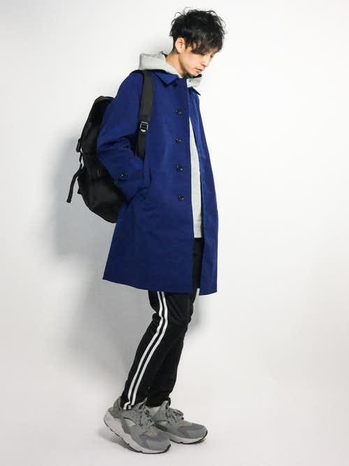 青ステンカラーコートとグレーパーカーの重ね着に黒リュックサックを合わせたコーディネート