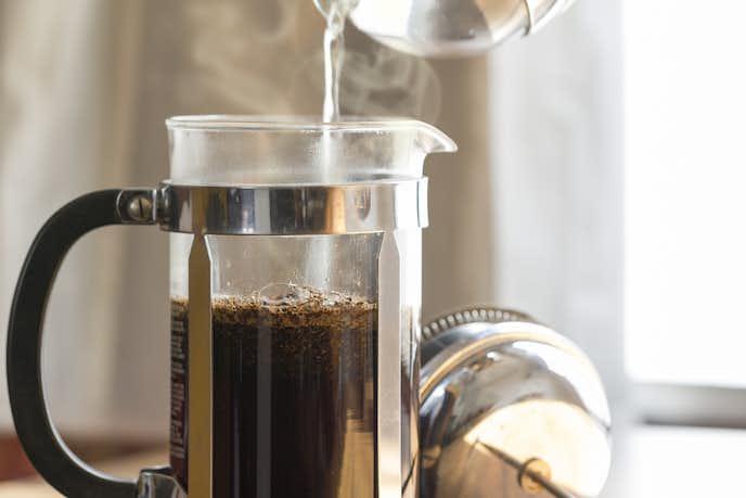 コーヒープレスにお湯を注ぐ人