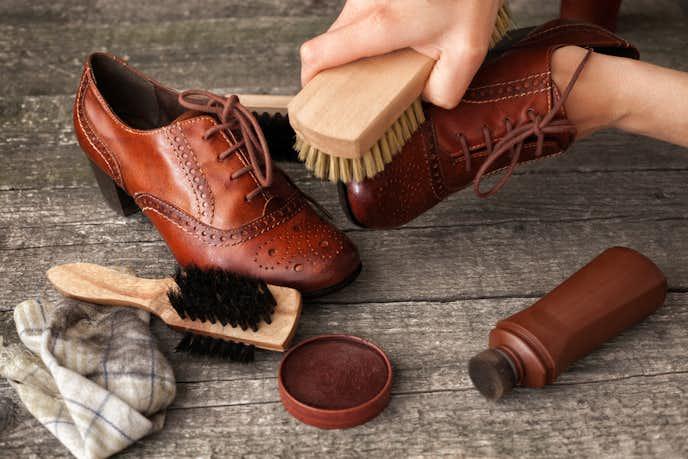 革靴を馬毛ブラシで手入れする人