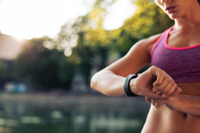 ランニングで走る時間を見ている女性