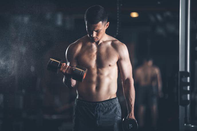 ダンベルカールで背筋を伸ばす男性