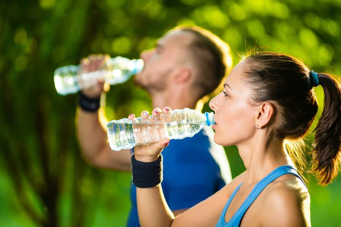 ランニングやジョギングで水分補給をしている男女