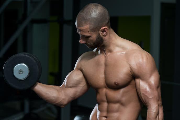 ダンベルカールで二の腕を見る男性