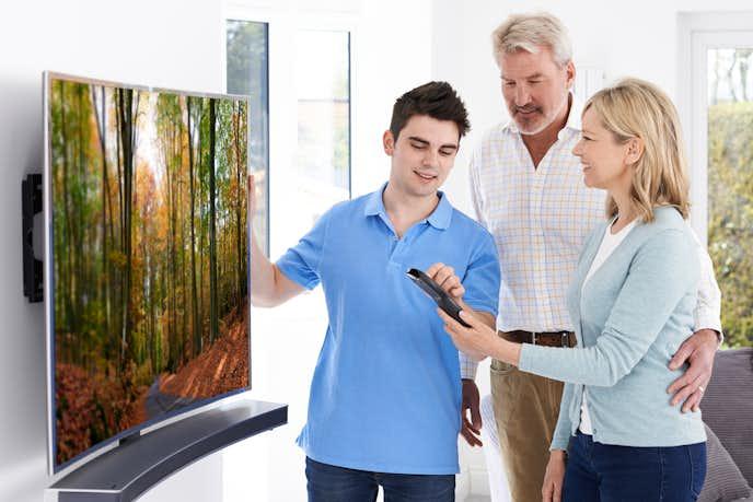 4Kテレビの前に立つ大人3人