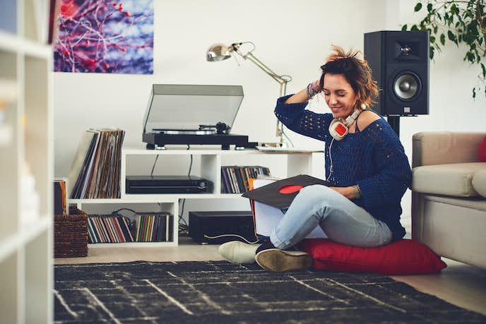レコードプレイヤーで音楽を聴いている女性