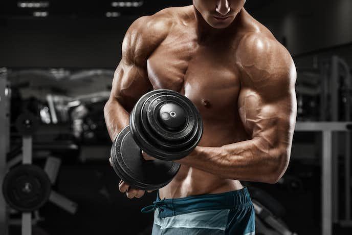 大胸筋をダンベルで鍛えている男
