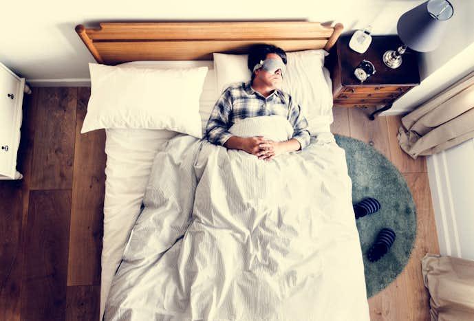 アイピローで目元の疲労を解消している男性
