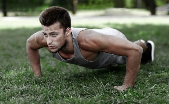 ワイドプッシュアップを草原で行っている男性