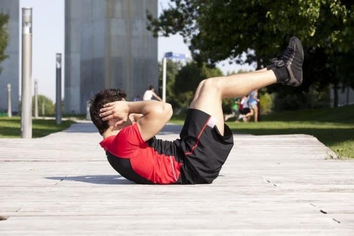 バイシクルクランチのスタートポジションを作っている男性