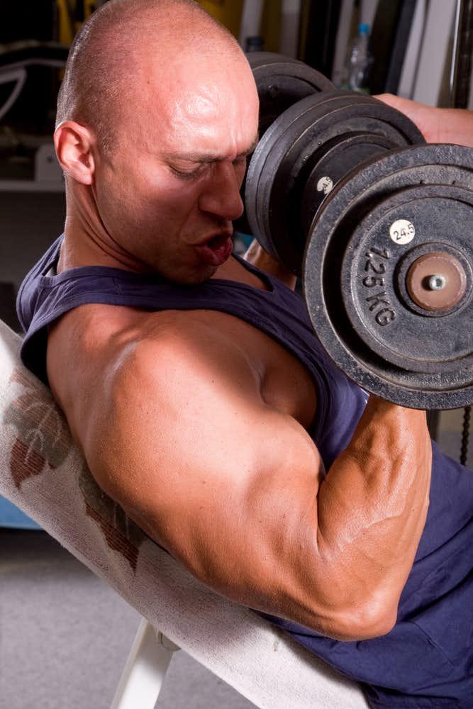 インクラインダンベルカールで腕を鍛えている