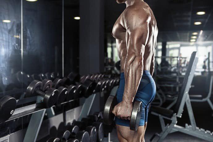 ダンベルサイドベントで腹斜筋を鍛えている男性