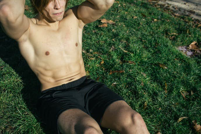ニートゥチェストトレーニング中に呼吸をしている男性